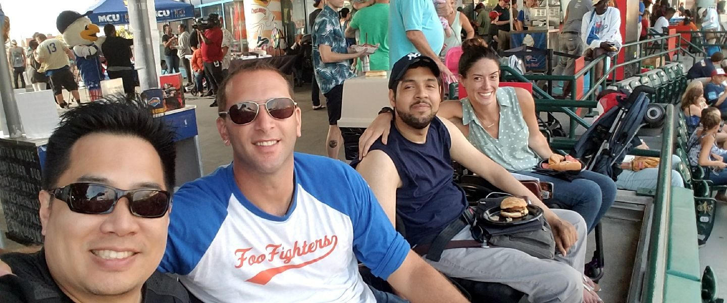3 men and a woman in wheelchairs at a baseball game.